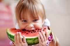 Lustiges Kind, das Wassermelone isst Stockbild