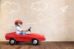 Lustiges Kind, das zu Hause Spielzeugauto f?hrt lizenzfreies stockfoto
