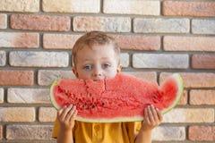 Lustiges Kind, das zuhause Wassermelone isst Stockbild