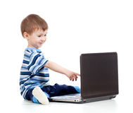Lustiges Kind, das zum Laptop sich berührt Lizenzfreie Stockfotos