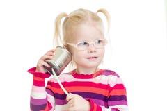 Lustiges Kind in den Brillen unter Verwendung einer Dose als Telefon Lizenzfreie Stockfotos