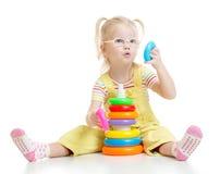 Lustiges Kind in den eyeglases, die bunte Pyramide spielen Lizenzfreies Stockfoto