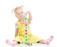 Lustiges Kind in den eyeglases, die Turm unter Verwendung der Blöcke machen Stockbilder