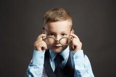 Lustiges Kind in den Gläsern und im siut Genie Kinder stockbild