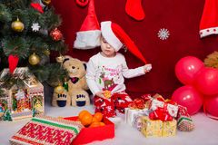 Lustiges Kind entfernt seine Weihnachtskappe Stockfotos