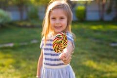 Lustiges Kind mit Süßigkeitslutscher, das glückliche kleine Mädchen, das großen Zuckerlutscher isst, Kind essen Bonbons stockbilder