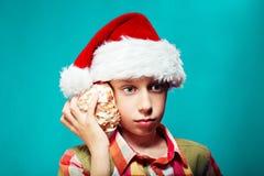 Lustiges Kind Sankt, die ein großes Seeoberteil hält Weihnachtsniederlassung und -glocken Lizenzfreie Stockbilder