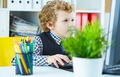 Lustiges Kind sieht wie ein Chef aus, der an Computer arbeitet lizenzfreies stockbild