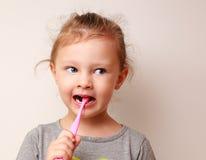 Lustiges Kindermädchen, das die Zähne putzt Stockfoto