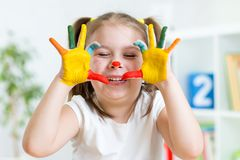 Lustiges Kindermädchen, das mit Farbfarben spielt Stockbild