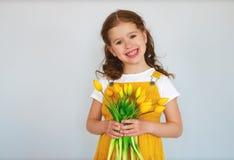 Lustiges Kindermädchen mit Blumenstrauß von gelben Blumen auf grauem Hintergrund stockfotos