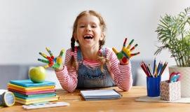 Lustiges Kindermädchen zeichnet die lachenden Showhände, die mit Farbe schmutzig sind lizenzfreies stockfoto