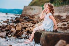 Lustiges Kindermädchen, das mit Wasserspritzen auf dem Strand spielt Reisen auf Sommerferien Lizenzfreie Stockbilder