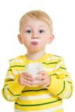 Lustiges Kindertrinkmilch vom Glas Stockfoto
