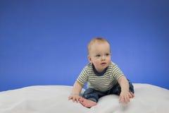 Lustiges kleines Baby, sitzend auf der weißen Decke, Atelieraufnahme, lokalisiert auf blauem Hintergrund Stockbilder