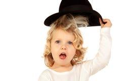 Lustiges kleines blondes Kind mit schwarzem Hut Lizenzfreie Stockfotos