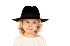 Lustiges kleines blondes Kind mit schwarzem Hut Stockbilder