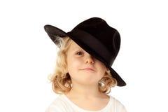 Lustiges kleines blondes Kind mit schwarzem Hut Stockbild