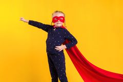 Lustiges kleines Energiesuperheld-Kindermädchen in einem roten Regenmantel und in einer Maske Superheldkonzept lizenzfreies stockfoto