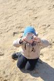 Lustiges kleines Kind, das eine Kompaktkamera hält Stockbild