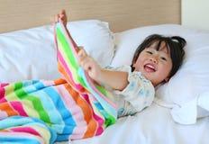Lustiges kleines Mädchen, das auf dem Bett mit Decke liegt stockfotografie