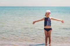 Lustiges kleines Mädchen, das auf dem Strand spielt Stockbilder