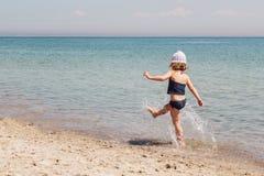 Lustiges kleines Mädchen, das auf dem Strand spielt Stockfoto