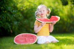 Lustiges kleines Mädchen, das draußen eine Scheibe der Wassermelone beißt Stockbild