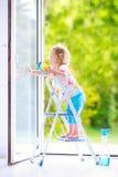 Lustiges kleines Mädchen, das ein Fenster wäscht Stockfotos