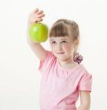 Lustiges kleines Mädchen, das einen grünen Apfel zeigt lizenzfreie stockbilder