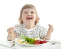Lustiges kleines Mädchen, das ihr Abendessen isst lizenzfreies stockfoto