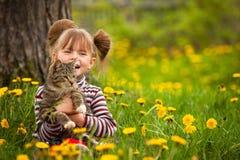 Lustiges kleines Mädchen, das mit einer Katze spielt Lizenzfreie Stockfotos