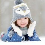 Lustiges kleines Mädchen, das Spaß im Winterpark hat Lizenzfreies Stockfoto