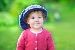 Lustiges kleines Mädchen in der großen Strickmütze im Garten Stockfotografie