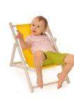 Lustiges kleines Mädchen im Studio auf gelbem deckchair Lizenzfreie Stockbilder