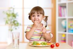 Lustiges kleines Mädchen isst im Kindergarten zu Mittag lizenzfreies stockfoto