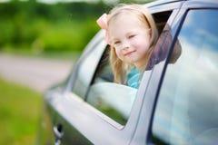 Lustiges kleines Mädchen ist das Haften ihr vorangehen heraus das Autofenster Lizenzfreie Stockfotografie