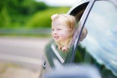 Lustiges kleines Mädchen ist das Haften ihr vorangehen heraus das Autofenster Lizenzfreie Stockfotos
