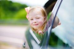 Lustiges kleines Mädchen ist das Haften ihr vorangehen heraus das Autofenster Stockfotografie