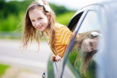 Lustiges kleines Mädchen ist das Haften ihr vorangehen heraus das Autofenster Stockfotos