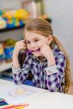 Lustiges kleines Mädchen mit dem blonden Haar, das bei Tisch sitzt und purpurroten Bleistift in ihrem Mund hält stockfotografie