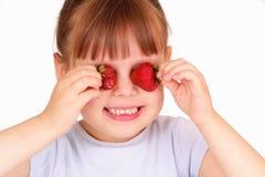 Lustiges kleines Mädchen mit Erdbeeren lizenzfreie stockbilder