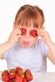 Lustiges kleines Mädchen mit geschmackvollen Erdbeeren lizenzfreie stockfotos