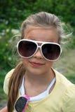 Lustiges kleines Mädchen mit großen Gläsern Lizenzfreies Stockfoto