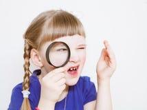 Lustiges kleines Mädchen mit Lupe stockfotografie