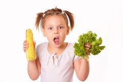 Lustiges kleines Mädchen mit Mais und Kopfsalat stockfotos