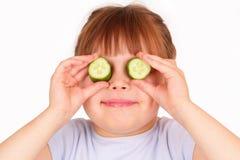 Lustiges kleines Mädchen mit Stücken der Gurke stockbilder