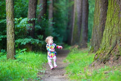 Lustiges kleines Mädchen in den Regenstiefeln gehend in einen Park Stockfotografie