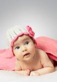 Lustiges kleines neugeborenes Baby, das einen Hut mit Blume trägt Stockbilder