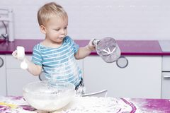 Lustiges Kleinkind auf der Küche, die mit Mehl spielt Stockbild